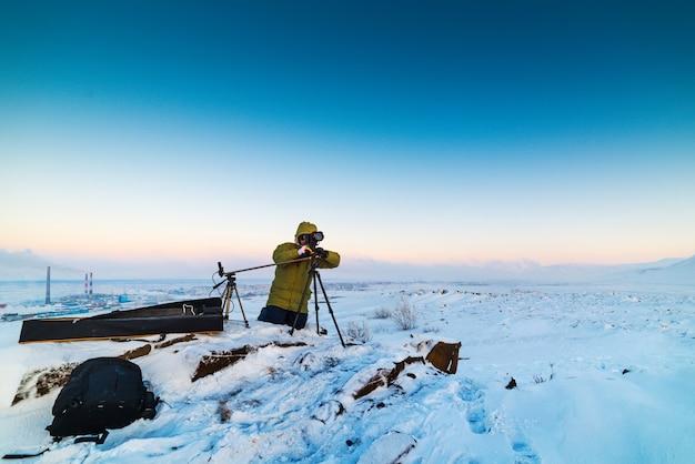 Mann mit fotokamera auf stativ, das zeitrafferfotos in der arktischen tundra macht. schlechte lichtverhältnisse.