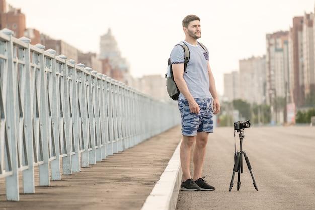 Mann mit fotokamera auf stativ, das zeitrafferfotos in der stadt macht