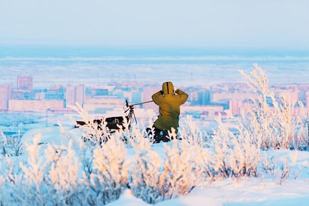Mann mit fotokamera auf stativ, das zeitrafferfotos winterpanorama der stadt macht. schlechte lichtverhältnisse.