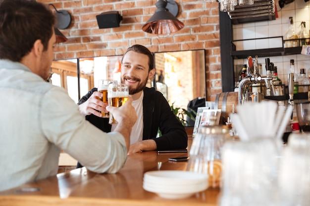 Mann mit freund trinkt bier in der bar