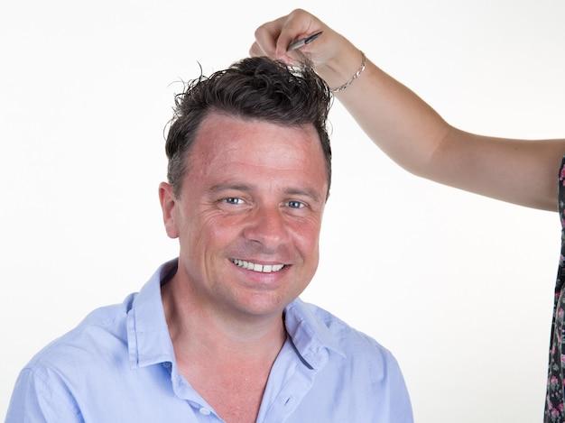 Mann mit friseur, der haarschnitt am schönheitssalon macht.