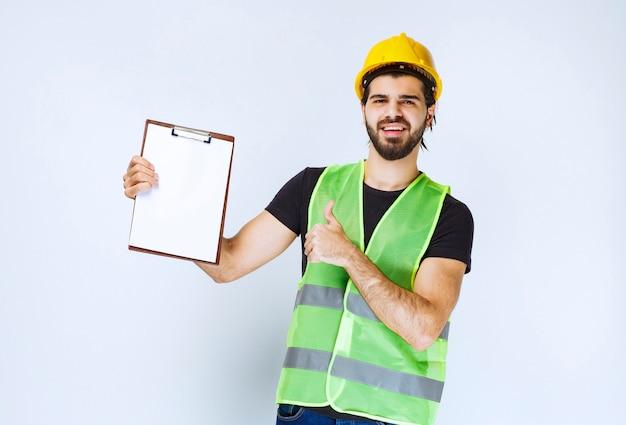 Mann mit gang, der den projektordner hält und zufriedenheitszeichen zeigt.