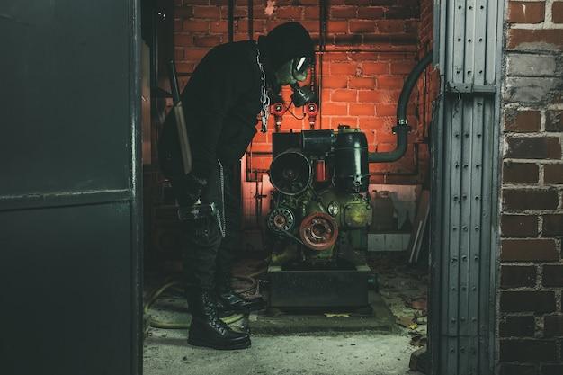 Mann mit gasmaske und einem hammer im maschinenraum.