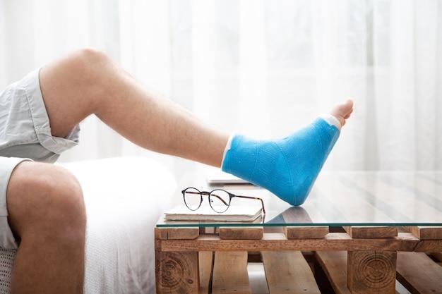 Mann mit gebrochenem bein in blauer schiene zur behandlung von verletzungen durch verstauchung des sprunggelenks beim lesen von büchern bei der häuslichen rehabilitation.