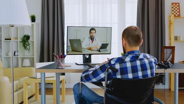 Mann mit gehbehinderung im rollstuhl, der mit seinem arzt per videoanruf spricht.