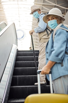 Mann mit gehstock und frau mit gepäck stehen auf der rolltreppe