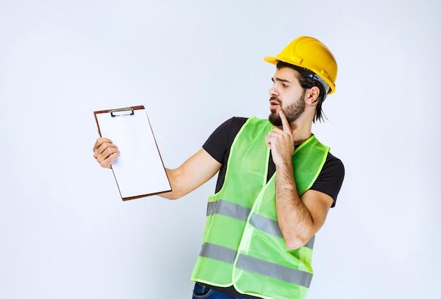 Mann mit gelbem helm, der die berichte über den ordner überprüft.