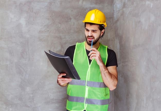 Mann mit gelbem helm und ausrüstung, der den berichtsordner überprüft und nachdenklich aussieht