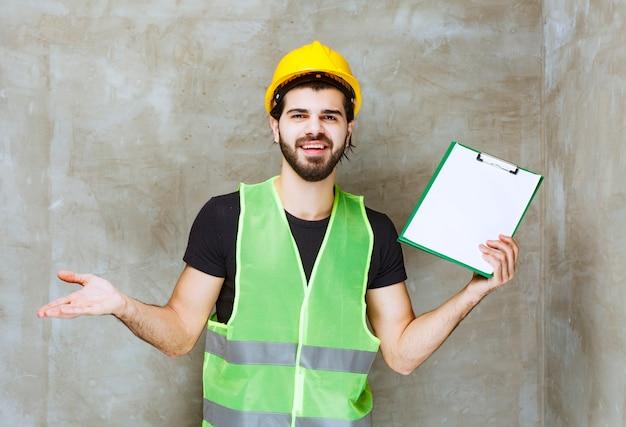 Mann mit gelbem helm und ausrüstung, der einen projektplan hält und verwirrt aussieht