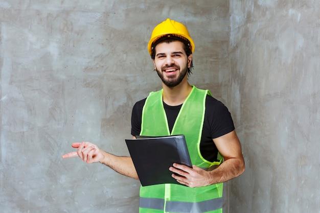 Mann mit gelbem helm und ausrüstung, der einen schwarzen berichtsordner hält und auf die reparierte wand zeigt