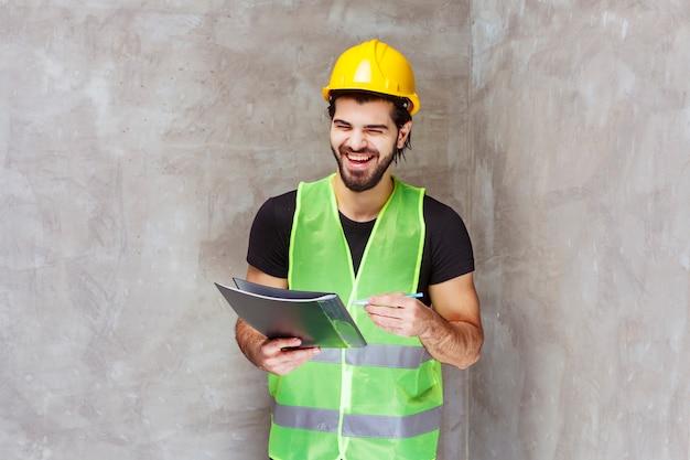 Mann mit gelbem helm und ausrüstung, der einen schwarzen berichtsordner hält und lächelt