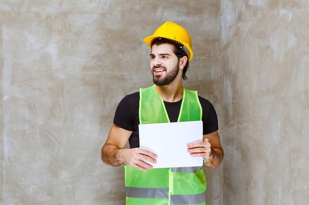 Mann mit gelbem helm und ausrüstung, der projektberichte hält