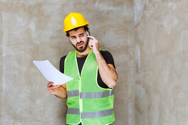 Mann mit gelbem helm und ausrüstung hält die projektberichte und sieht unsicher und nachdenklich aus