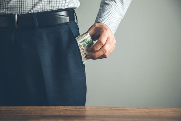Mann mit geld in der tasche auf grau