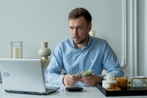 Mann mit geld und einem taschenrechner prüft rechnungen berechnet ausgaben studiert das guthaben am tisch zu hause sitzen