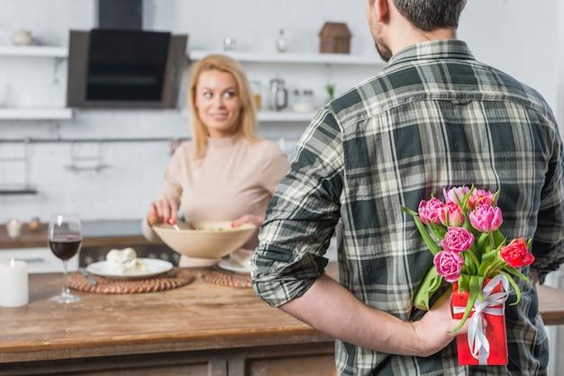 Mann mit geschenk und blumen von hinten und frau in der küche