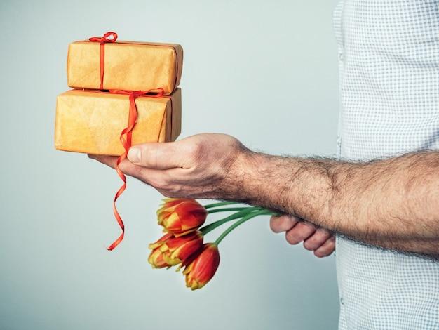 Mann mit geschenken und blumen