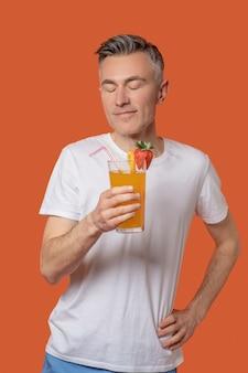 Mann mit geschlossenen augen mit glas fruchtcocktail