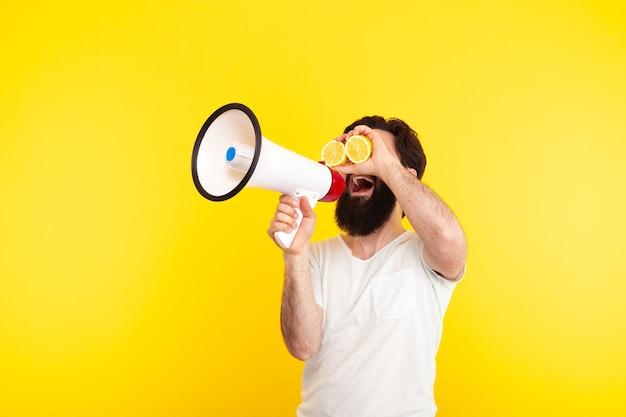 Mann mit geschnittener zitrone auf den augen, schreiend durch ein megaphon