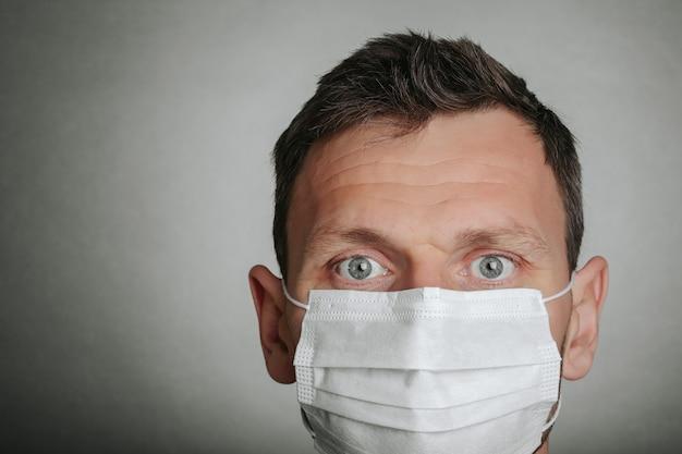 Mann mit gesichtsmaske auf grauem hintergrund. coronavirus und luftverschmutzung pm2.5 konzept. covid-19