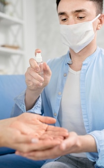 Mann mit gesichtsmaske, die hände desinfiziert