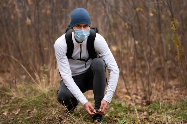 Mann mit gesichtsmaske im wald, der schnürsenkel bindet