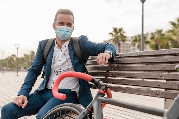 Mann mit gesichtsmaske sitzt auf einer bank neben seinem fahrrad im freien