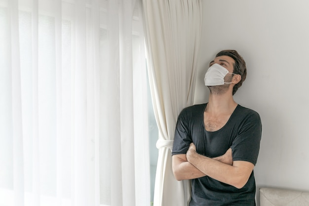 Mann mit gesichtsmaske zum schutz vor kopfschmerzen und husten wegen coronavirus covid-19 im quarantäneraum