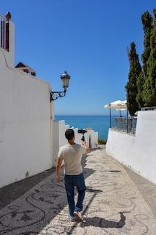 Mann mit gimbal für smartphone, der durch die straßen einer mittelmeerstadt geht
