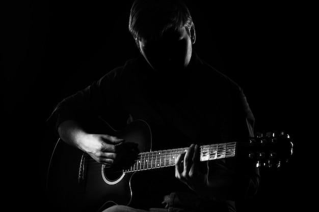 Mann mit gitarre in der dunkelheit