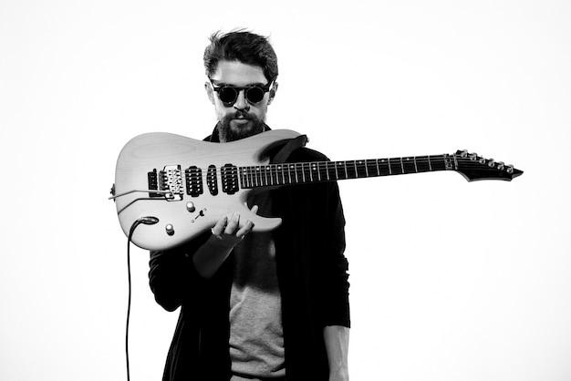 Mann mit gitarre in händen musiker rockstar auf einem hellen hintergrund