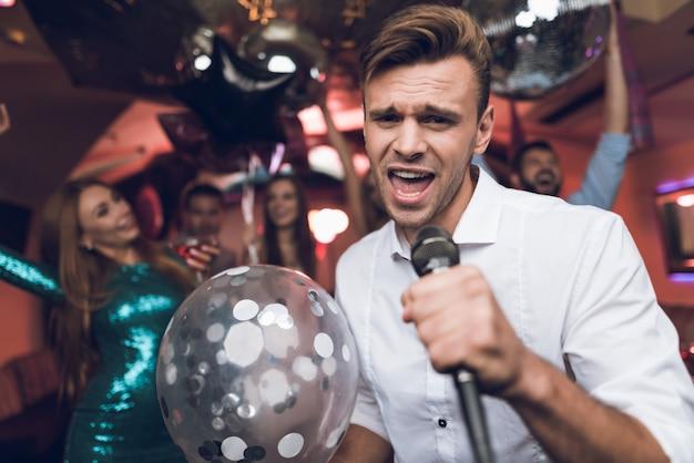 Mann mit glänzendem ballon singend im verein