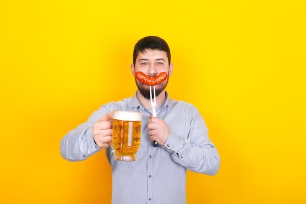 Mann mit glas bier und gegrillter wurst auf einer gabel