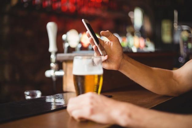 Mann mit glas bier unter verwendung des mobiltelefons im zähler