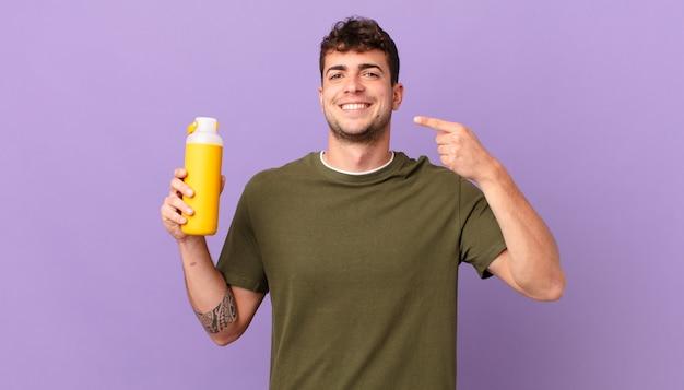 Mann mit glattem lächeln, das selbstbewusst auf sein eigenes breites lächeln zeigt, positive, entspannte, zufriedene haltung
