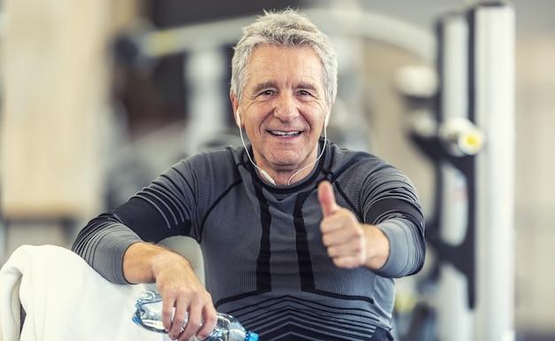 Mann mit grauen haaren hält nach dem training daumen hoch, um unabhängig vom alter fit zu bleiben.
