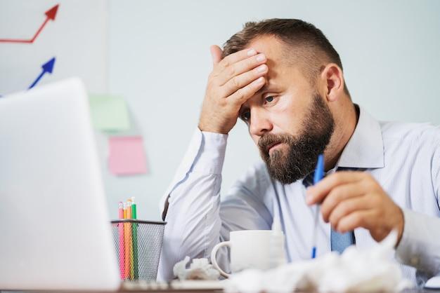 Mann mit grippe im büro arbeiten