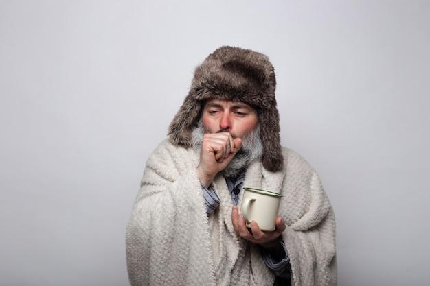 Mann mit grippe und husten geschützt mit hut und decke