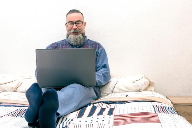 Mann mit großem bart, der auf dem bett in seinem schlafzimmer sitzt, pyjama-brille tragend und laptop benutzt
