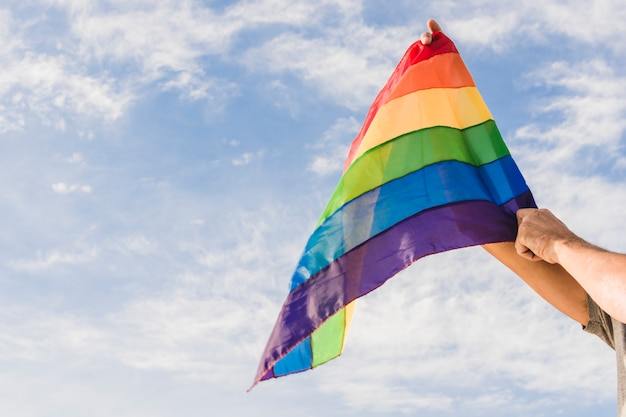 Mann mit großer flagge in den lgbt-farben und im blauen himmel