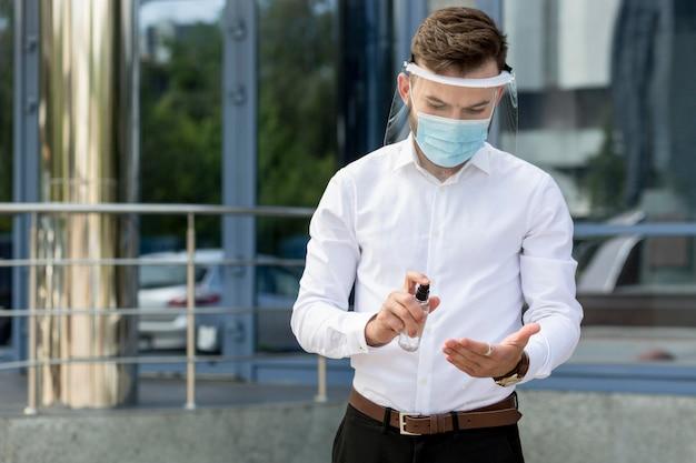 Mann mit händedesinfektionsmittel