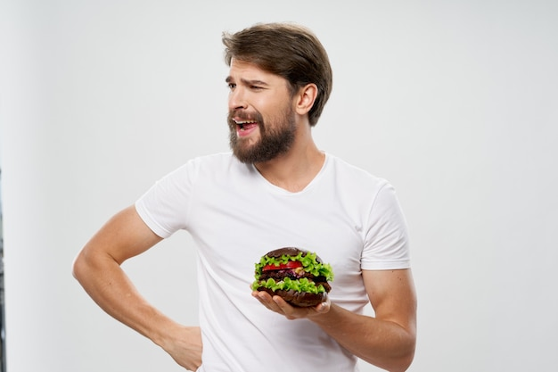Mann mit hamburger-fast-food-diät nahrungsaufnahme weißes t-shirt