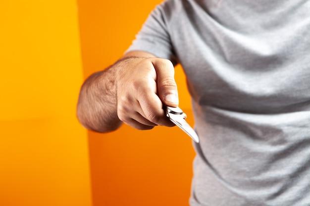 Mann mit handmesser auf orangem hintergrund
