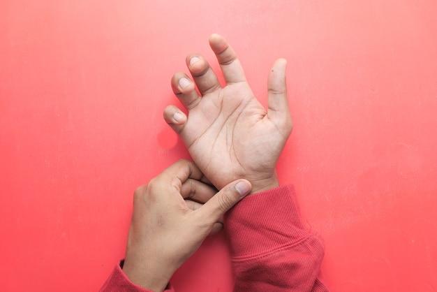 Mann mit handschmerzen auf rotem hintergrund
