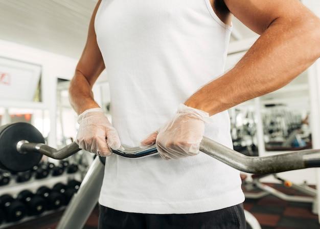 Mann mit handschuhen, die im fitnessstudio trainieren