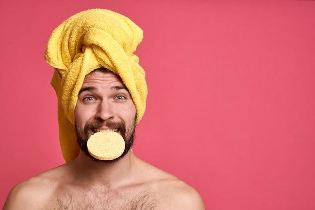 Mann mit handtuch auf dem kopf mit schwamm, der sein gesicht reinigt
