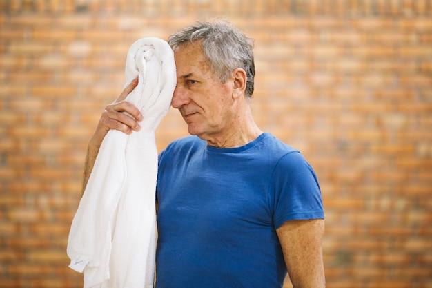 Mann mit handtuch in der turnhalle