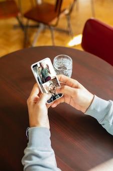 Mann mit handy für videoanruf beim trinken von wasser