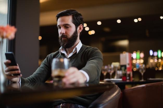 Mann mit handy in der bar