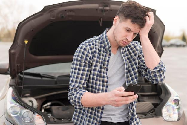 Mann mit handy neben kaputtem auto